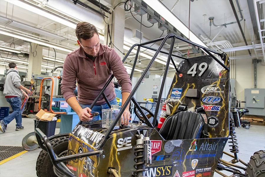 A student works on a Baja race car
