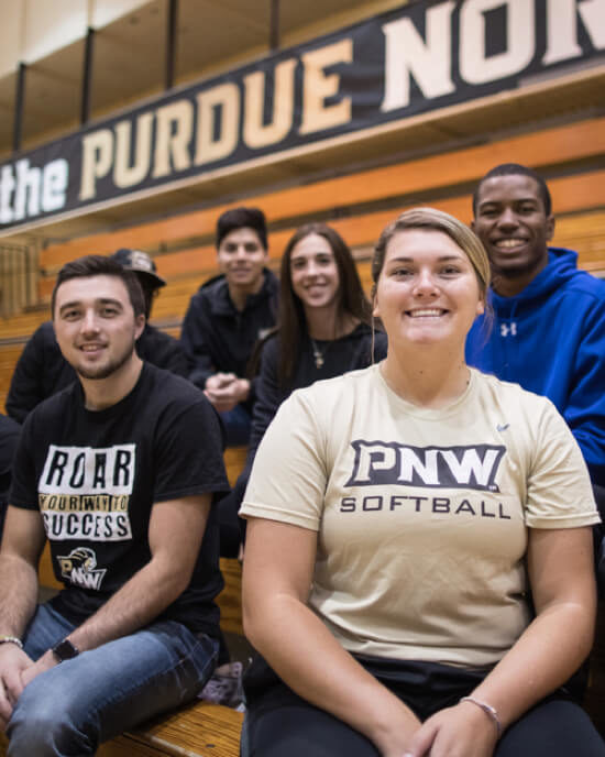 PNW students pose together in a gym, with one wearing a PNW softball shirt.