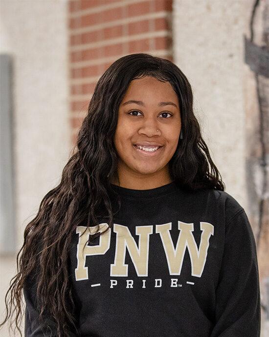 A PNW student wearing a PNW Pride sweatshirt