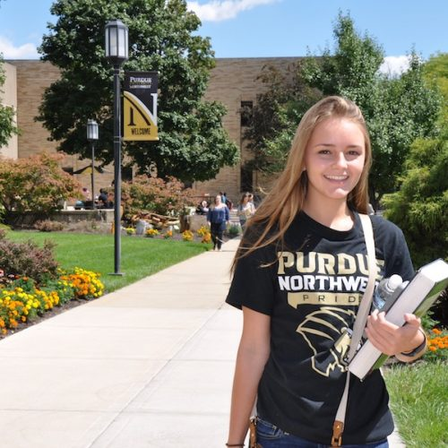 A student is smiling on campus.
