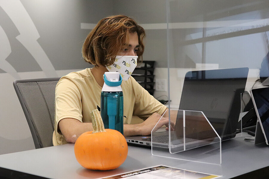 A student in a mask works on a computer