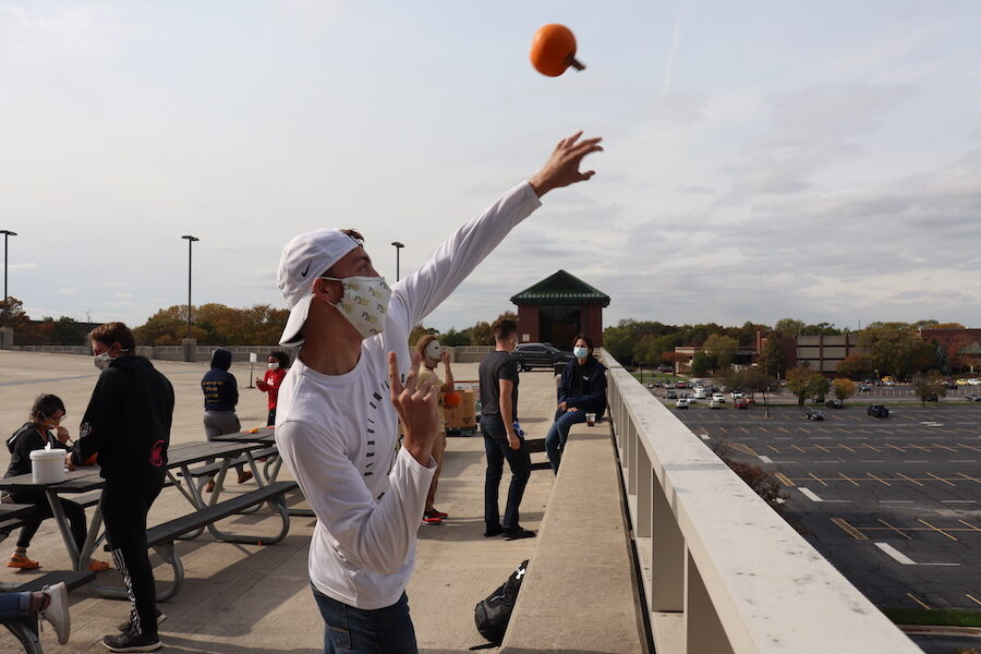 Students tossing pumpkins off roof.