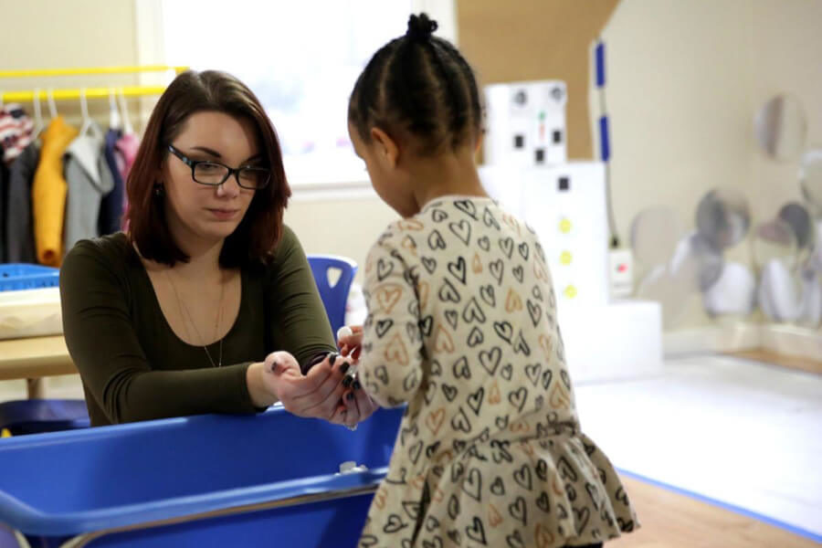 A teaching student works with a child.