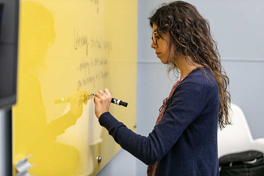 A student writes on a board.
