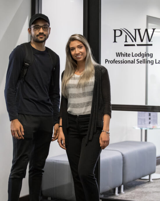 two standing students in front of PNW sign