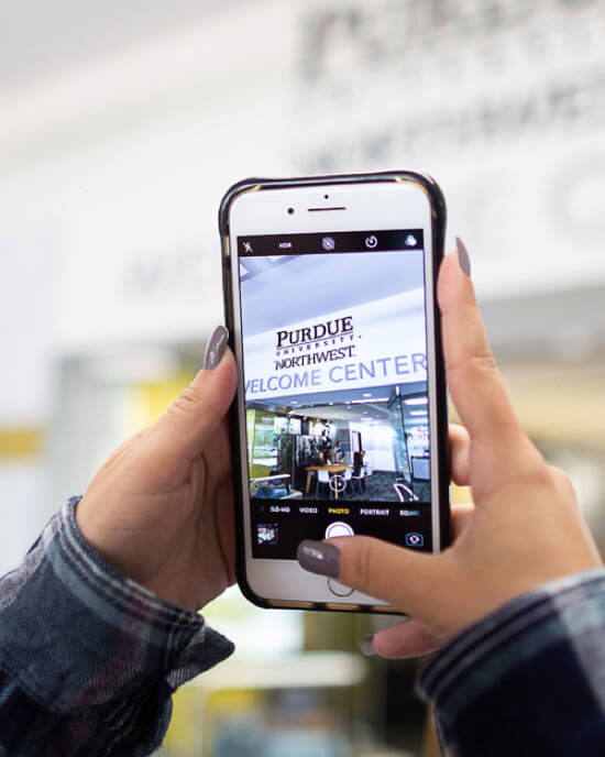 student holding cellphone with PNW image on it