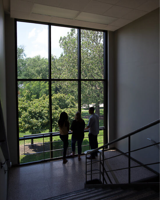 three students standing at hallway window