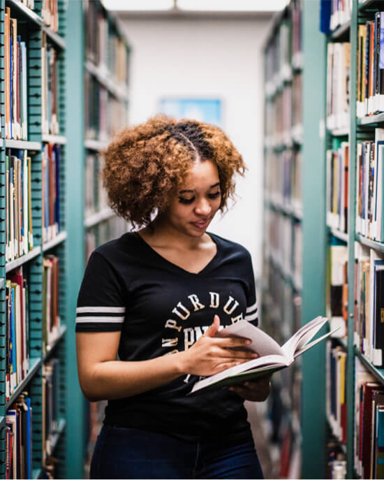 student looking at book in library stacks