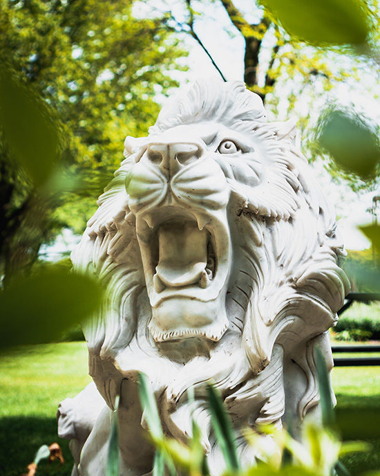 A lion sculpture surrounded by greenery.