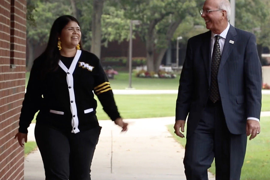 PNW MBA student Lily Andarcia and Chancellor Thomas Keon walk together on campus.