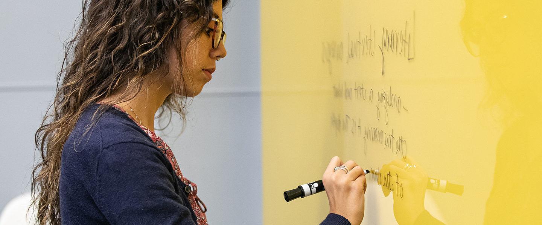 Female writing on a smart board