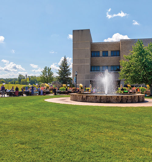 People gather in front of a building and fountain on PNW's Westville campus on a sunny day.