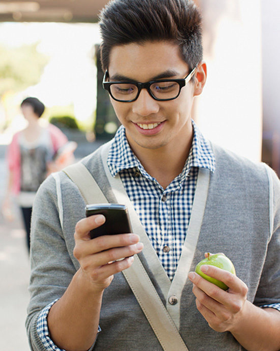 A student texts while holding an apple