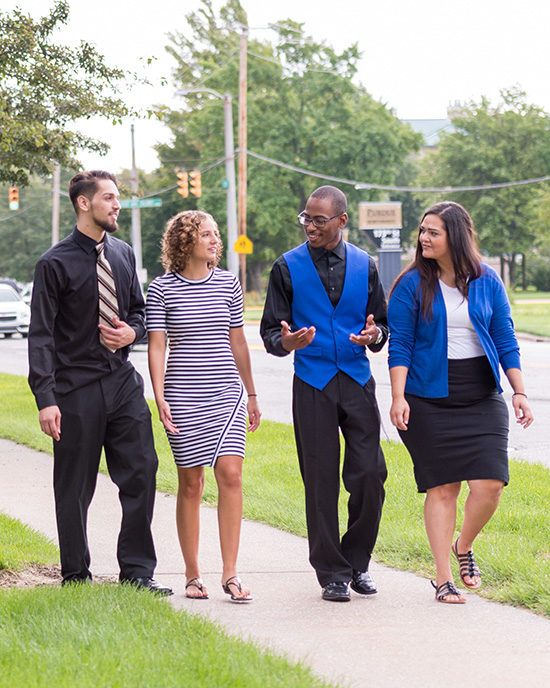 Students in dress clothes cross campus