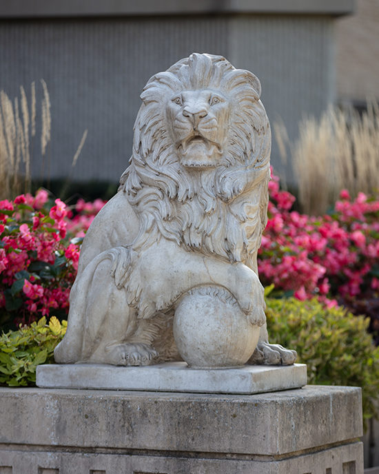A lion sculpture flanked by flowers