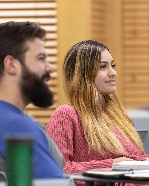 Two students listen in the classroom.
