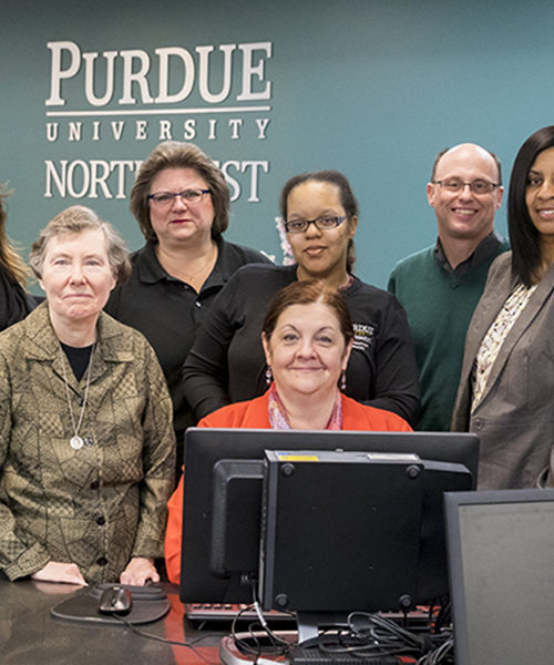Staff gather around the desk of the PNW library on Hammond campus.