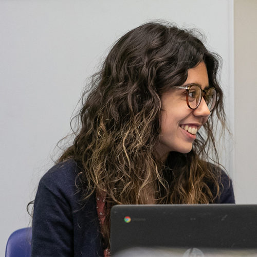 Student Madeline Clement smiles over her computer