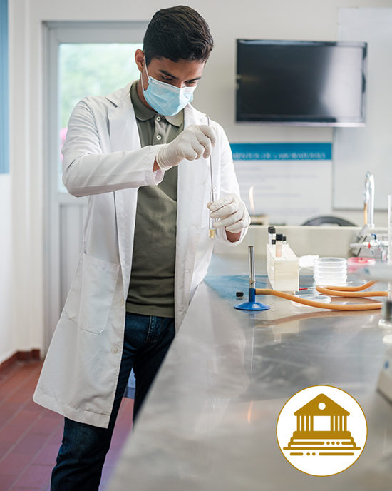 A student wearing a mask and gloves works with chemicals. An illustration on the photo shows a building