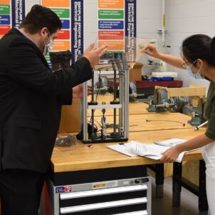 Afshin Zahraee, assistant professor, Mechanical Engineering Technology (left) and Ran Zhou, assistant professor of Mechanical Engineering examine a miniature tensile testing machine for 3D printed parts and specimen for potential use in Remote Knowledge Labs.