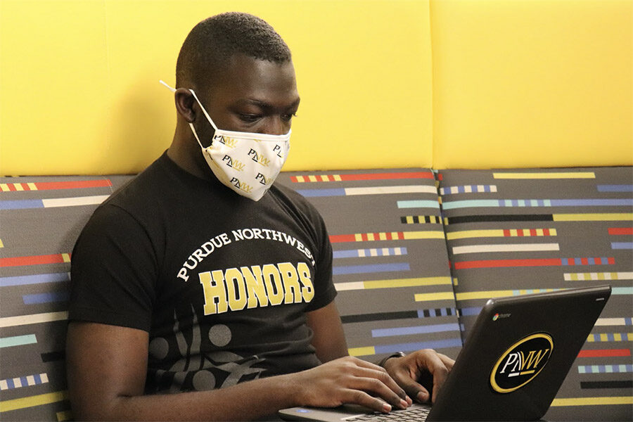 A student in a PNW Honors College T-Shirt wearing a mask works on a laptop