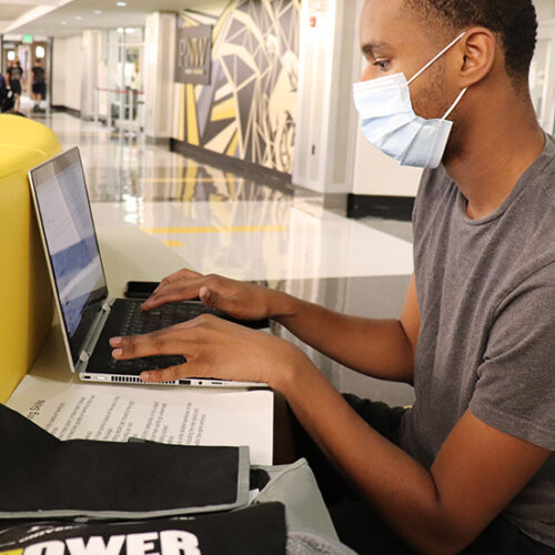 A PNW student wearing a mask works on a laptop.