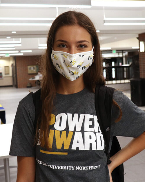 A student wears a PNW mask and Power Onward shirt in PNW's Student Union and Library Building.