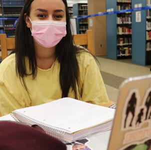 A PNW student wears a mask in the Westville library