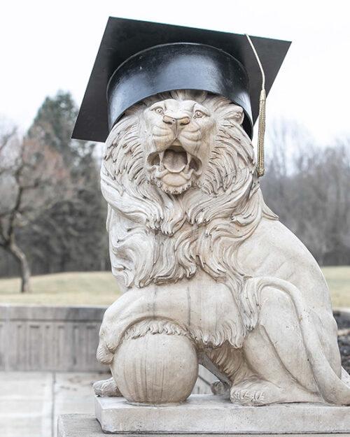 A PNW Lion Sculpture wearing a commencement cap