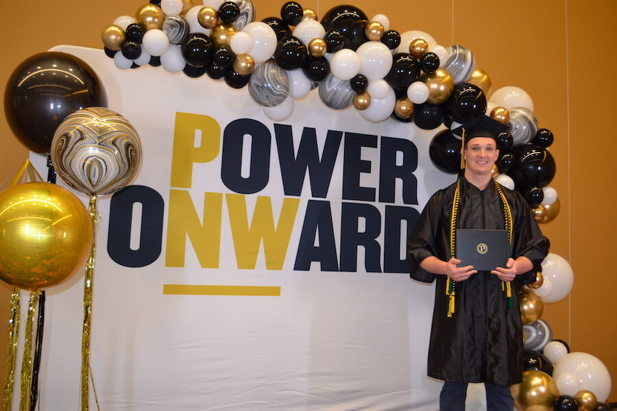 A student pictured in front of Power Onward sign.