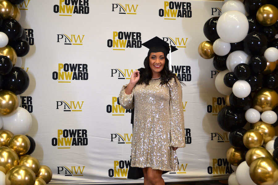 A PNW graduate is pictured in front of the step and repeat.