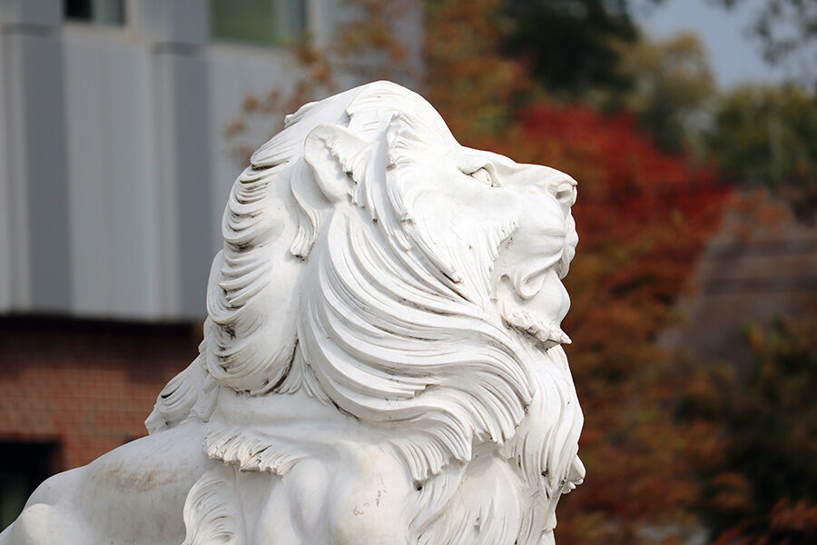 A lion sculpture in front of fall foliage