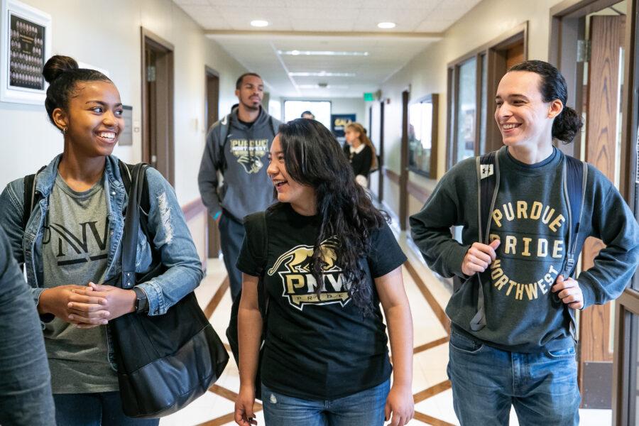 PNW students walk down a hallway wearing PNW gear