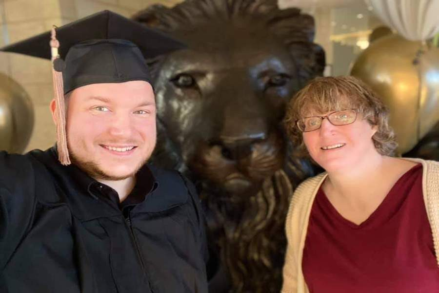 PNW Graduate Timothy Paul poses with a PNW lion and a family member.