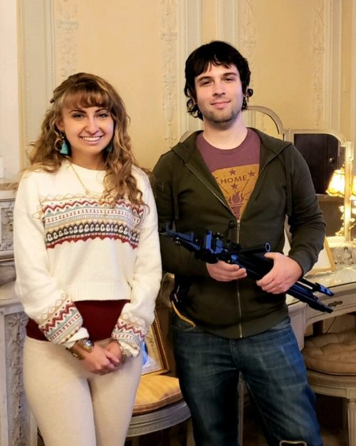 Woman and Man holding filming equipment in mansion