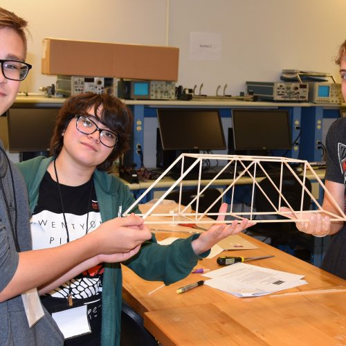 Ayden Wollweber, Vivianna Ruiz and Timothy Pierce display their wooden bridge project created at the high school camp in 2019.