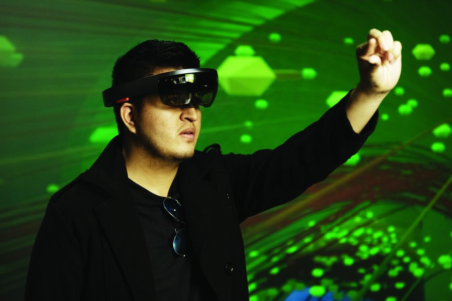 A student wearing goggles stands in front of a green background