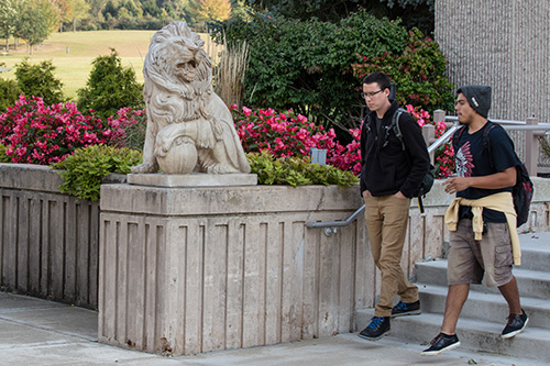 PNW students walk past a lion sculpture on the Westville campus
