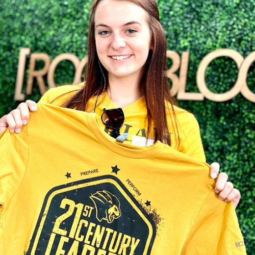 A student holds a 21st century leaders shirt.