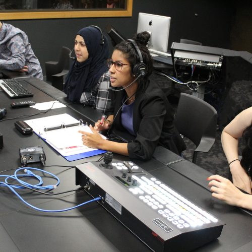 PNW broadcast students sit at the production table