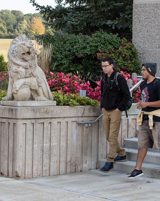 Students walk near a lion sculpture on PNW's Westville Campus