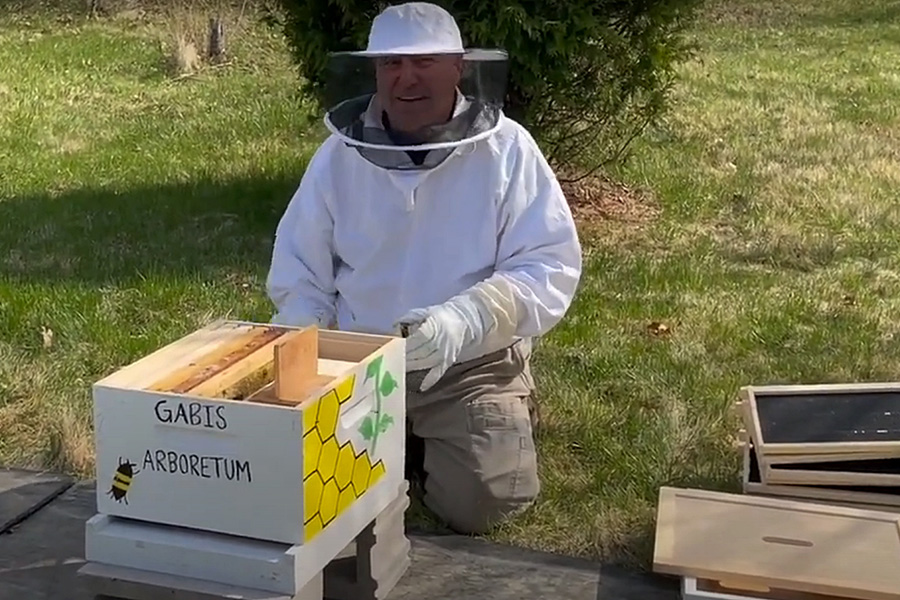 A beekeeper poses with a hive.