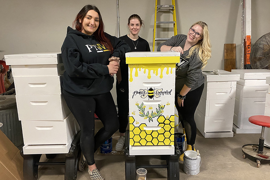 PNW students pose with their painted beehive.