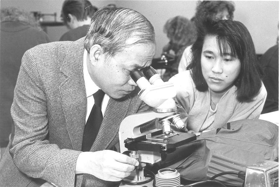 A professor looks through a microscope.