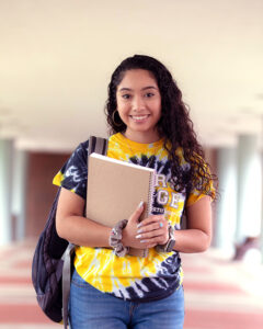 A PNW student in a tie-dye t-shirt holds her notebook outdoors.