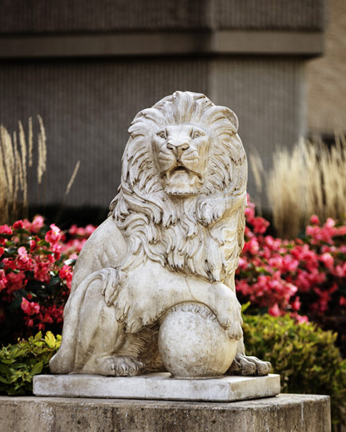 A lion statue in front of flowers