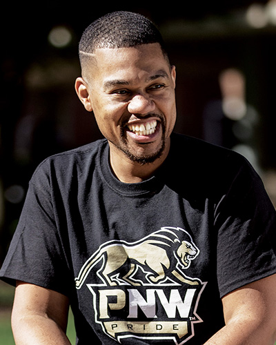 A smiling students in a PNW athletics shirt