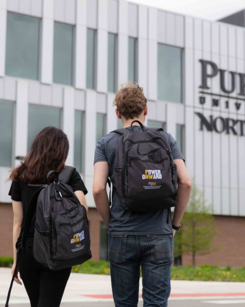 Two PNW students stand with their backs visible in front of the Nils K. Nelson Bioscience Innovation Building